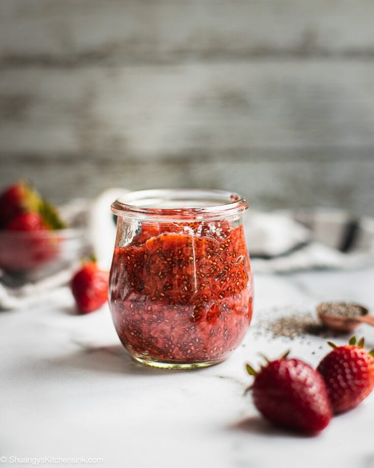 A jar of strawberry chia jam. There are a few strawberries on the side.