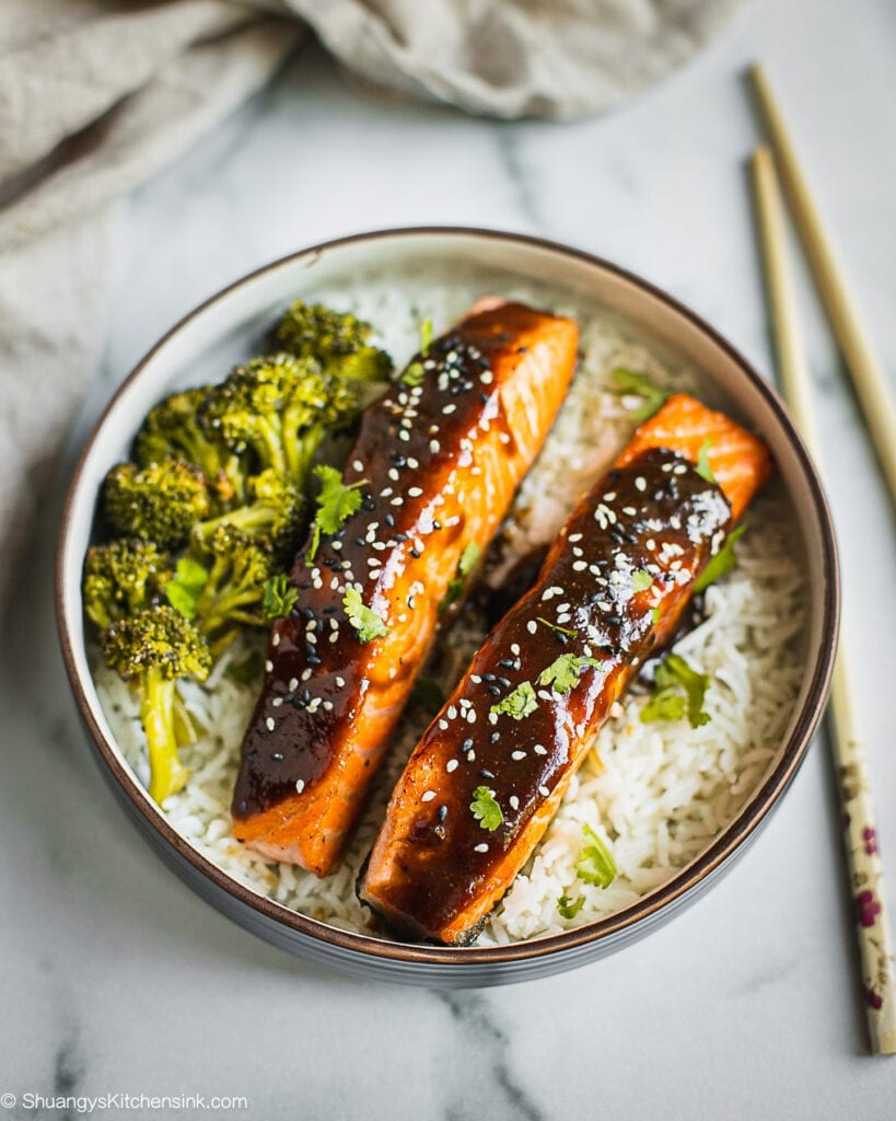 A bowl crispy teriyaki glazed salmon served with rice and broccoli. There are some black and white sesame on top.
