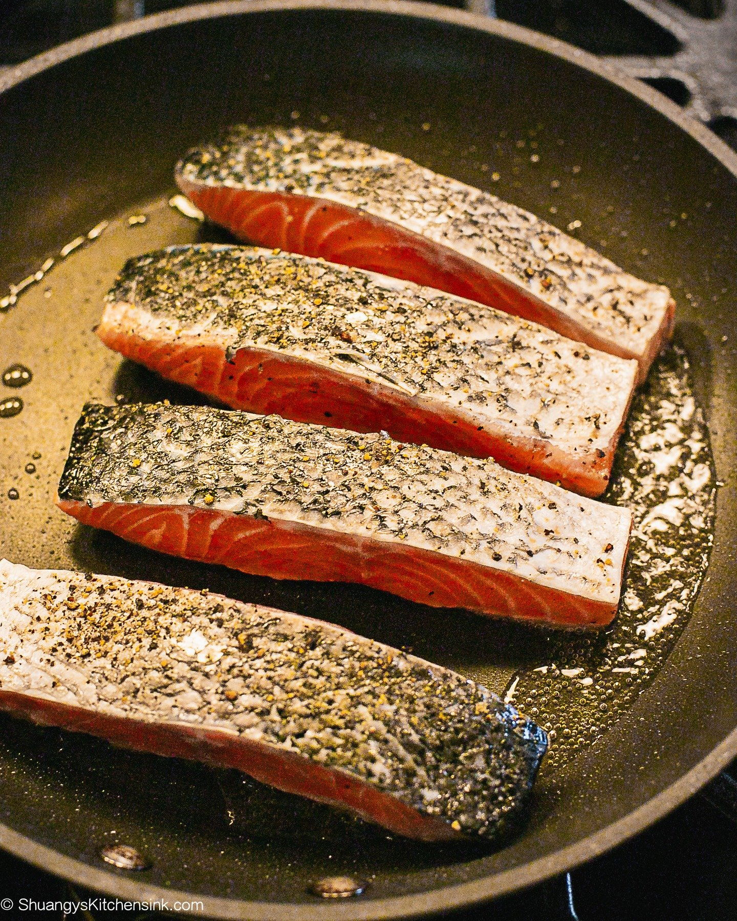 4 salmon fillets being seared in hot oil in a pan.