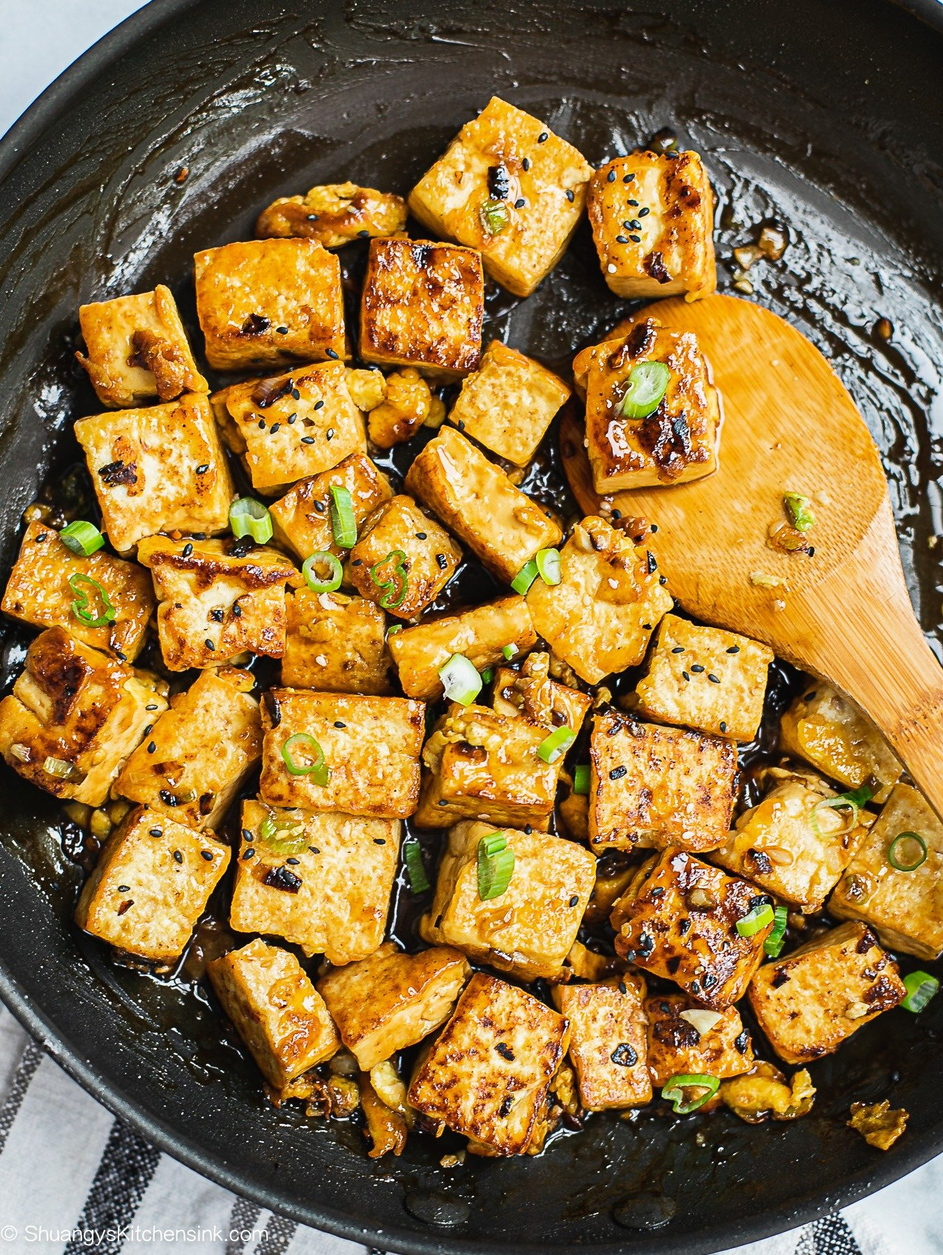 A pan of Asian Garlic Tofu stir fry freshly cooked and glazed with soy garlic sauce. Topped with scallion.