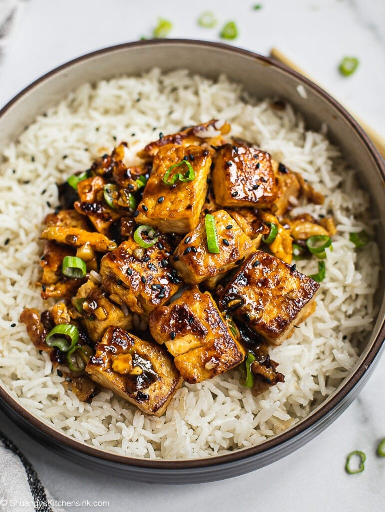 A bowl of Chinese Garlic Tofu stir fry on a bed of rice. Topped with scallion.
