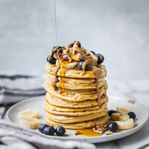 A stack of healthy buttermilk pancakes topped with bananas, blueberries, almond butter, and pecans. There is maple syrup dripping down from the top.