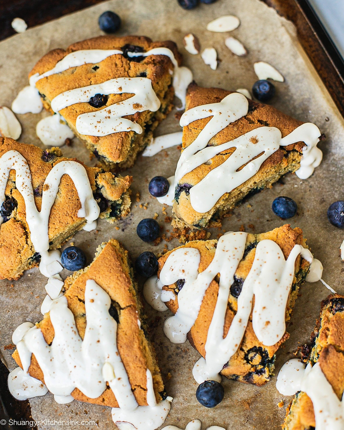 A few paleo blueberry scones with cashew cream cheese frosting. There are a few blueberries and almonds on the side.
