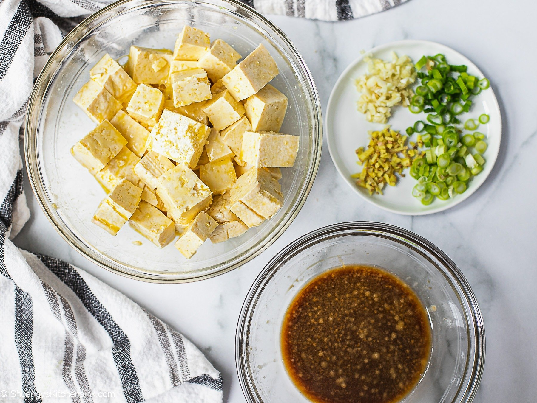 Ingredients to make a stir fry. one bowl of tofu cut in cubes, one bowl of soy sauce and a plate with ginger, scallions and garlic