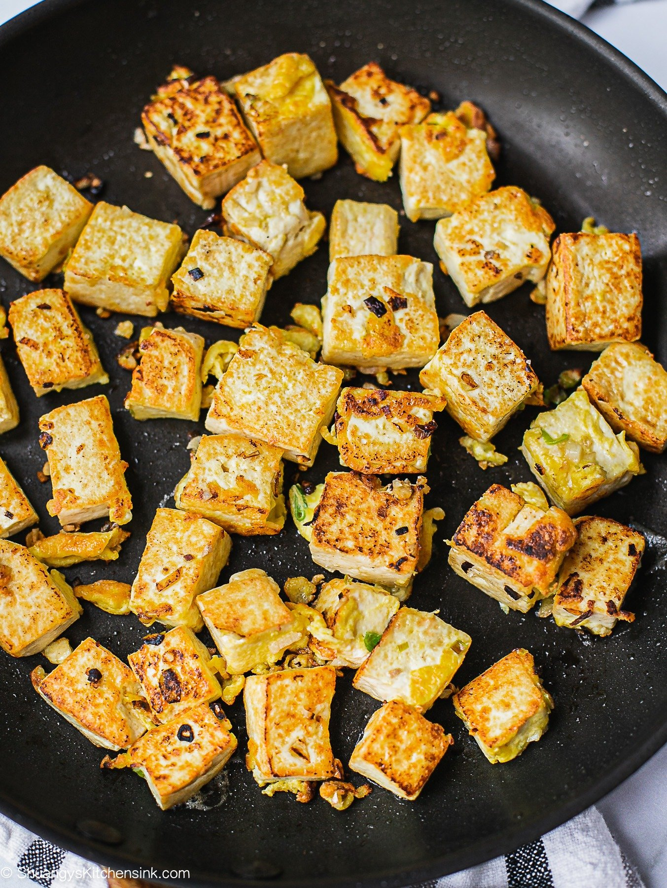 A pan of healthy Asian Garlic Tofu freshly cooked and glazed with soy garlic sauce. Topped with scallion.