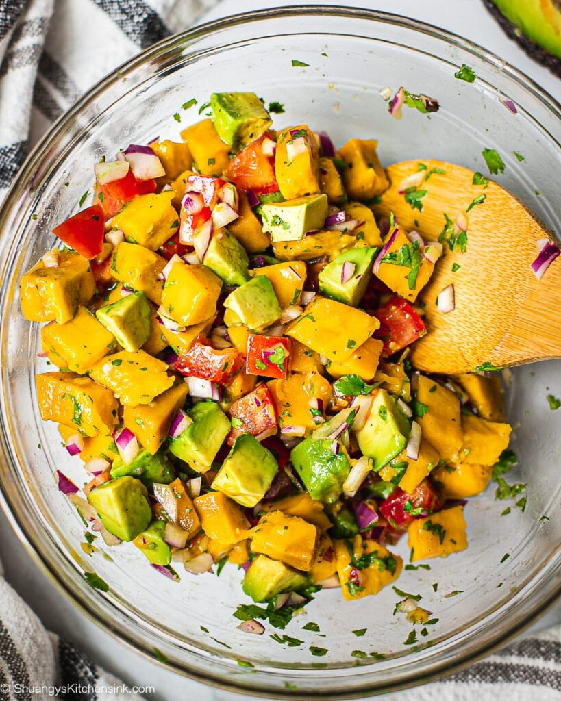 A bowl of fresh ingredients for mango avocado salsa that include fresh mango, avocado, red onion, tomatoes and cilantro.
