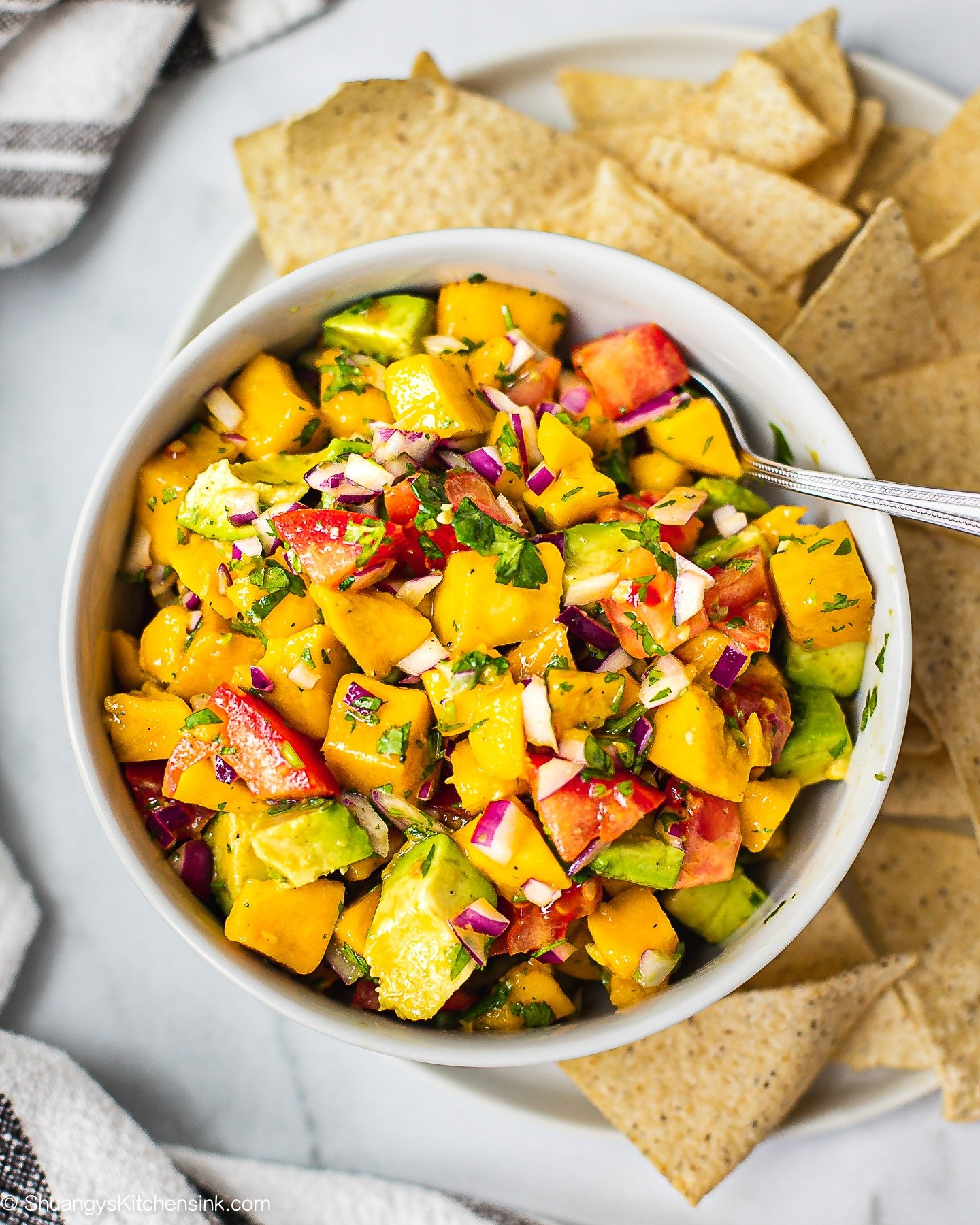 A bowl of fresh ingredients for mango avocado salsa that include fresh mango, avocado, red onion, tomatoes, diced jalapeno, and cilantro. There are chips on the side.