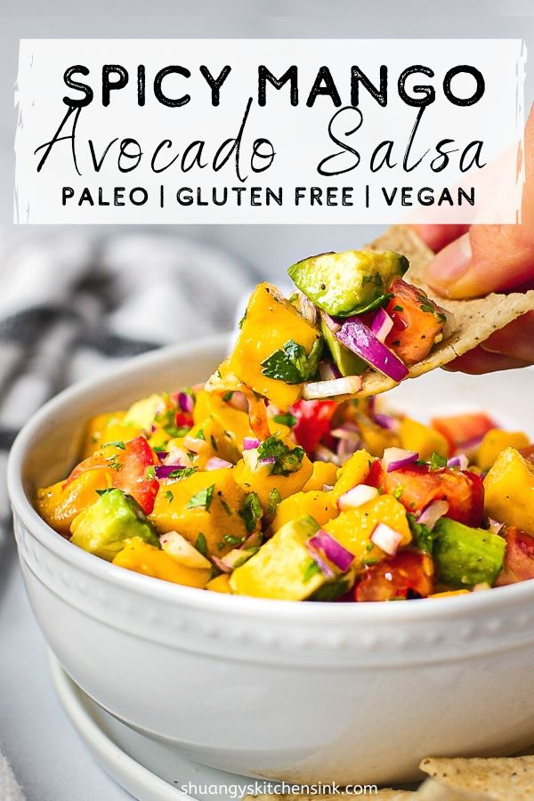 A bowl of fresh ingredients for mango avocado salsa that include fresh mango, avocado, red onion, tomatoes, diced jalapeno, and cilantro. There are chips on the side. A hand is digging in with some chips.