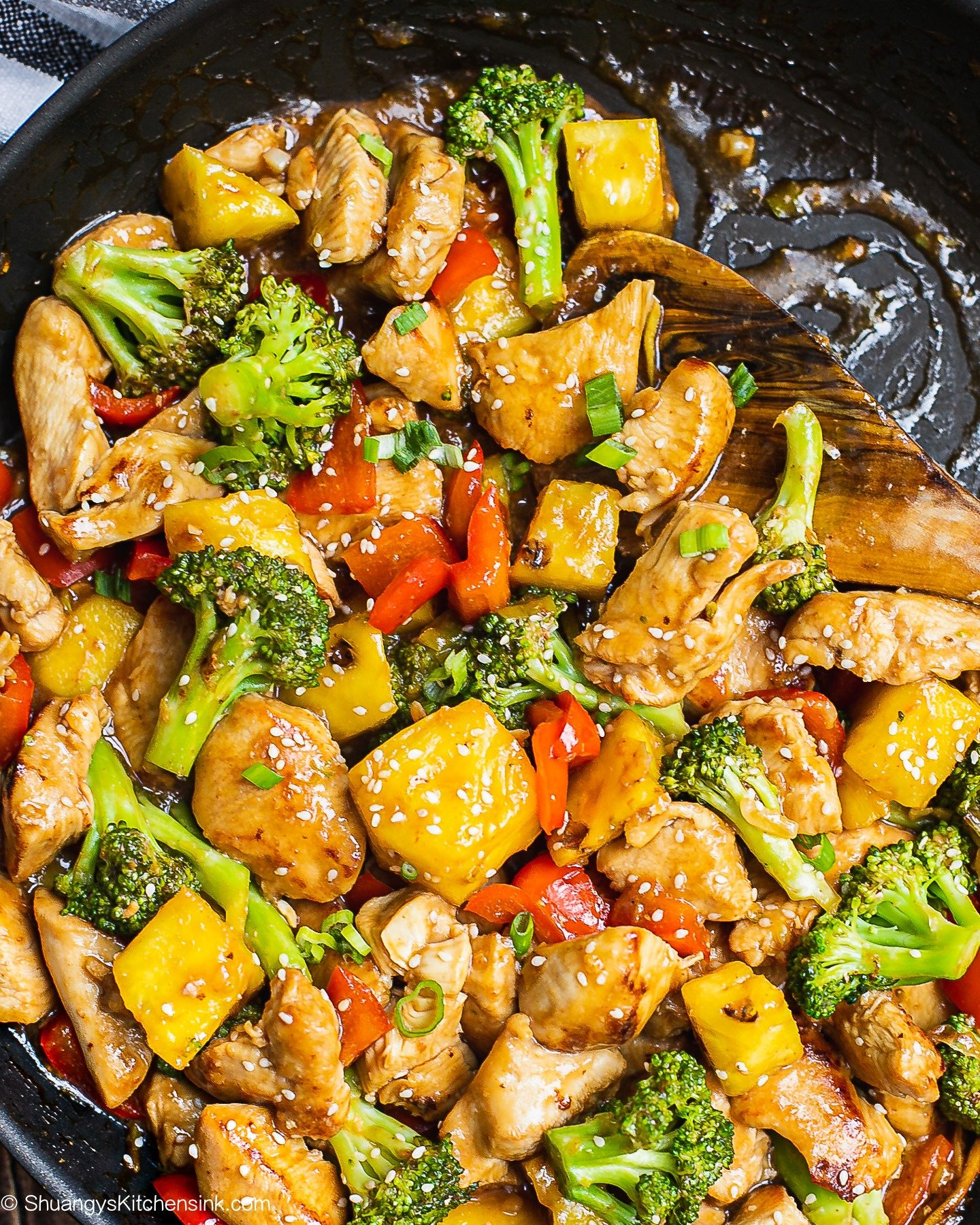 a stir fry of veggies, fruit and chicken glazed with teriyaki