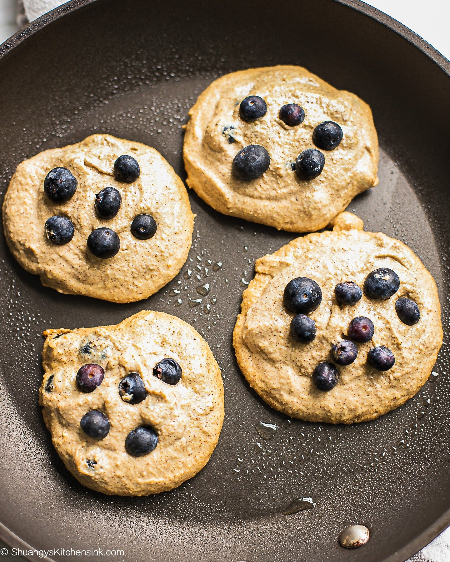 Vegan oatmeal pancakes are heating on a frying pan. There are some extra fresh blueberries on top.