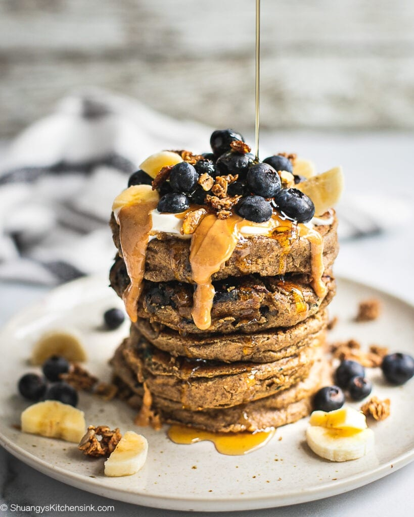A stack of gluten-free pancakes topped with peanut butter, blueberries, bananas and maple syrup