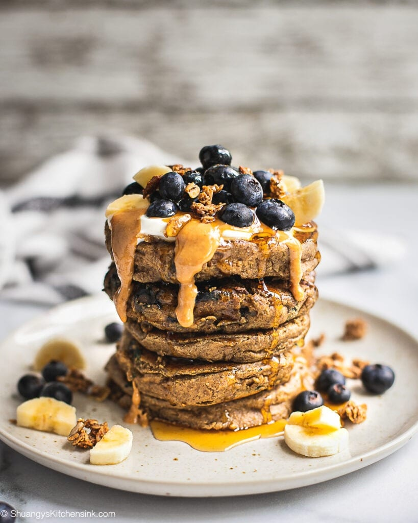A stack of vegan blueberry banana oatmeal pancakes topped with more fresh blueberries, bananas and maple syrup.