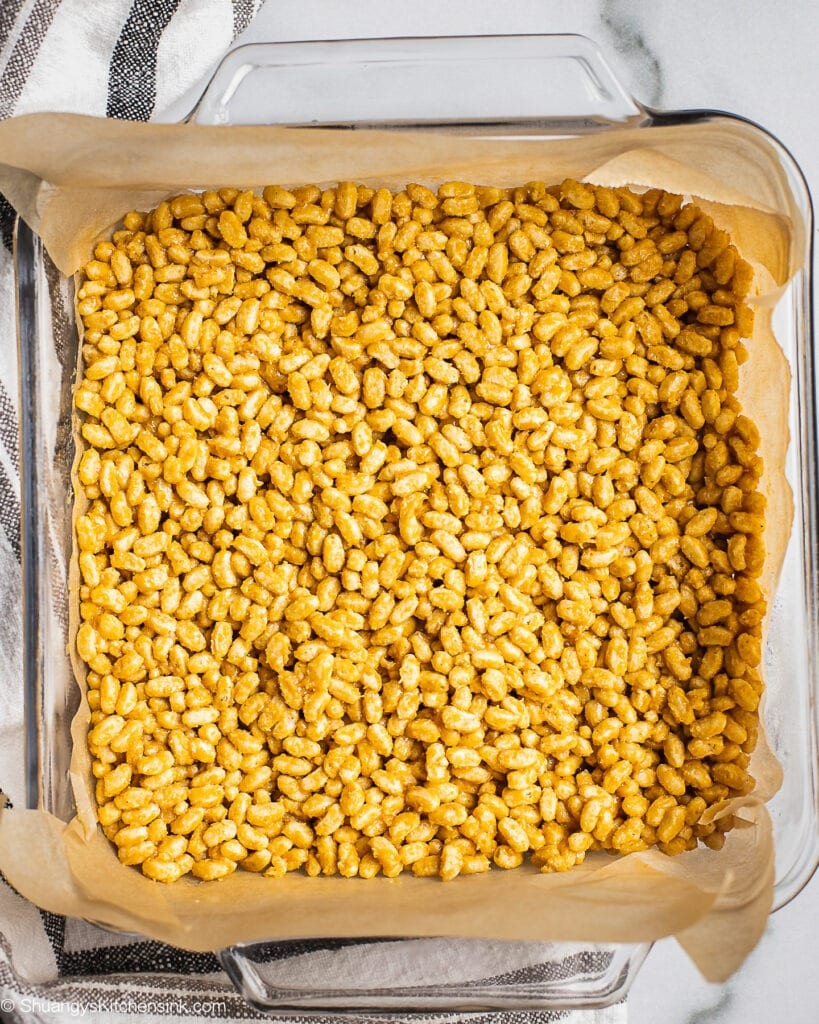 An 8x8 baking dish with a layer of peanut butter rice crispy cereal mixutre.