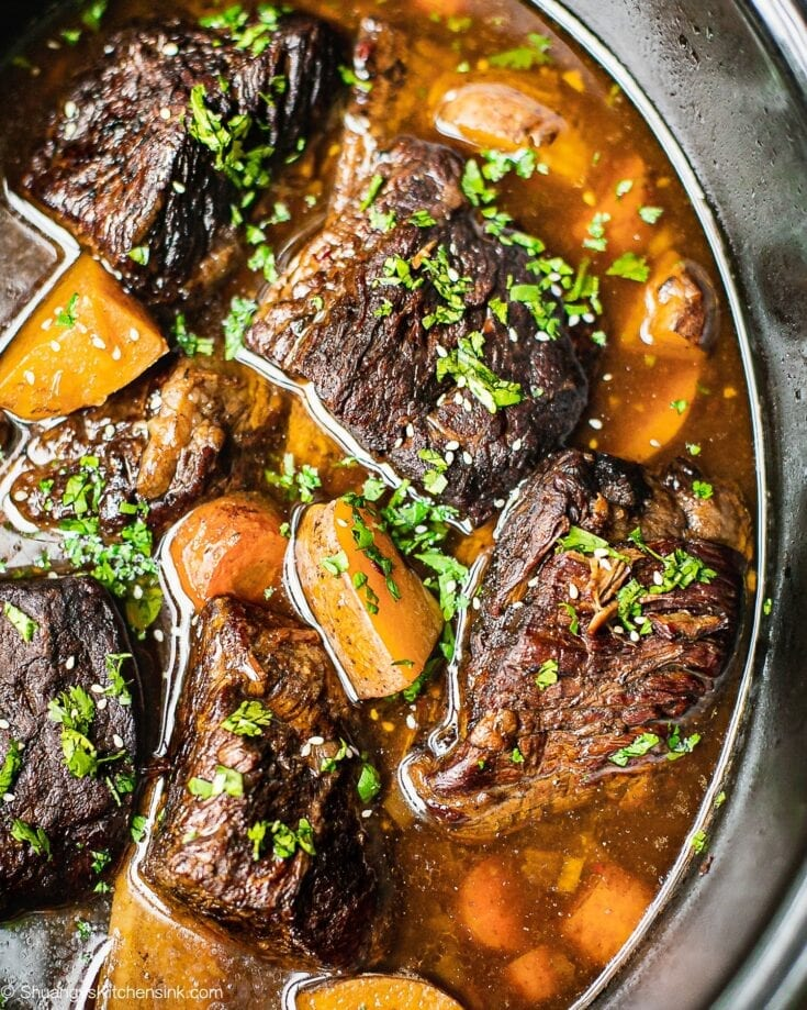 A crockpot full of Korean beef short ribs, potatoes, and carrots. It is garnished with cilantro.