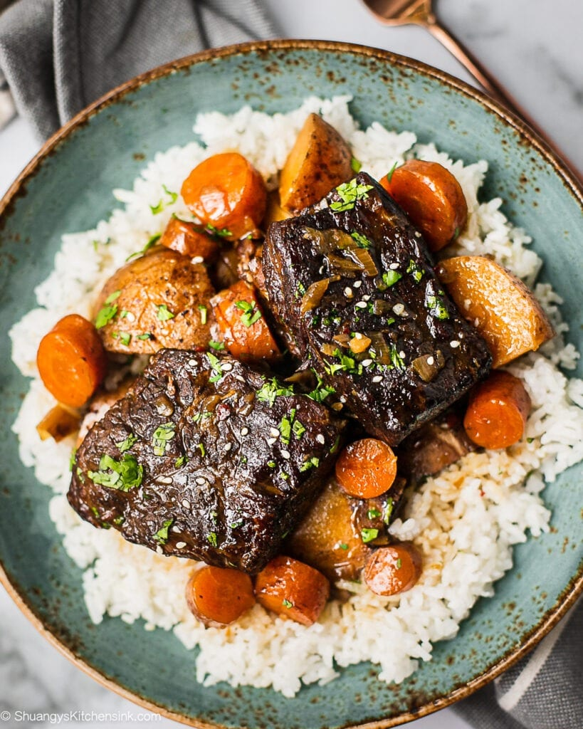 A plate of slow cooker Korean short ribs served with jasmine rice. There are carrots, potatoes in it and garnished with cilantro..
