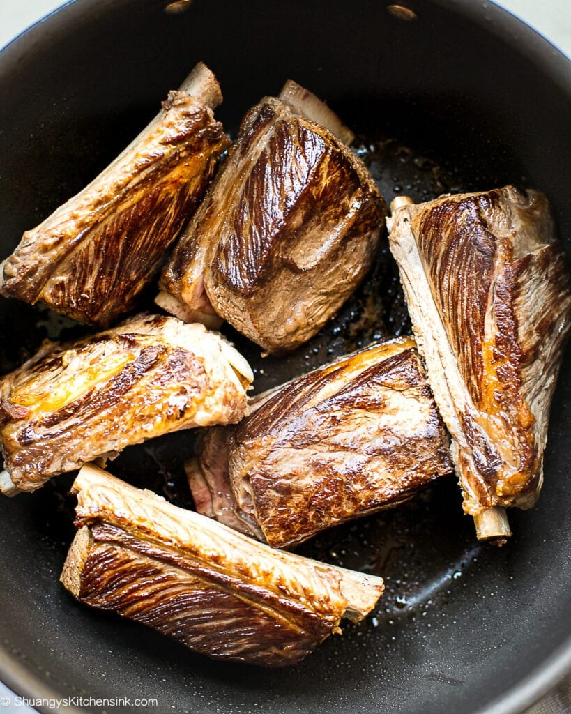 A few pieces of Beef short ribs in a heavy bottomed pot, seared to brown.
