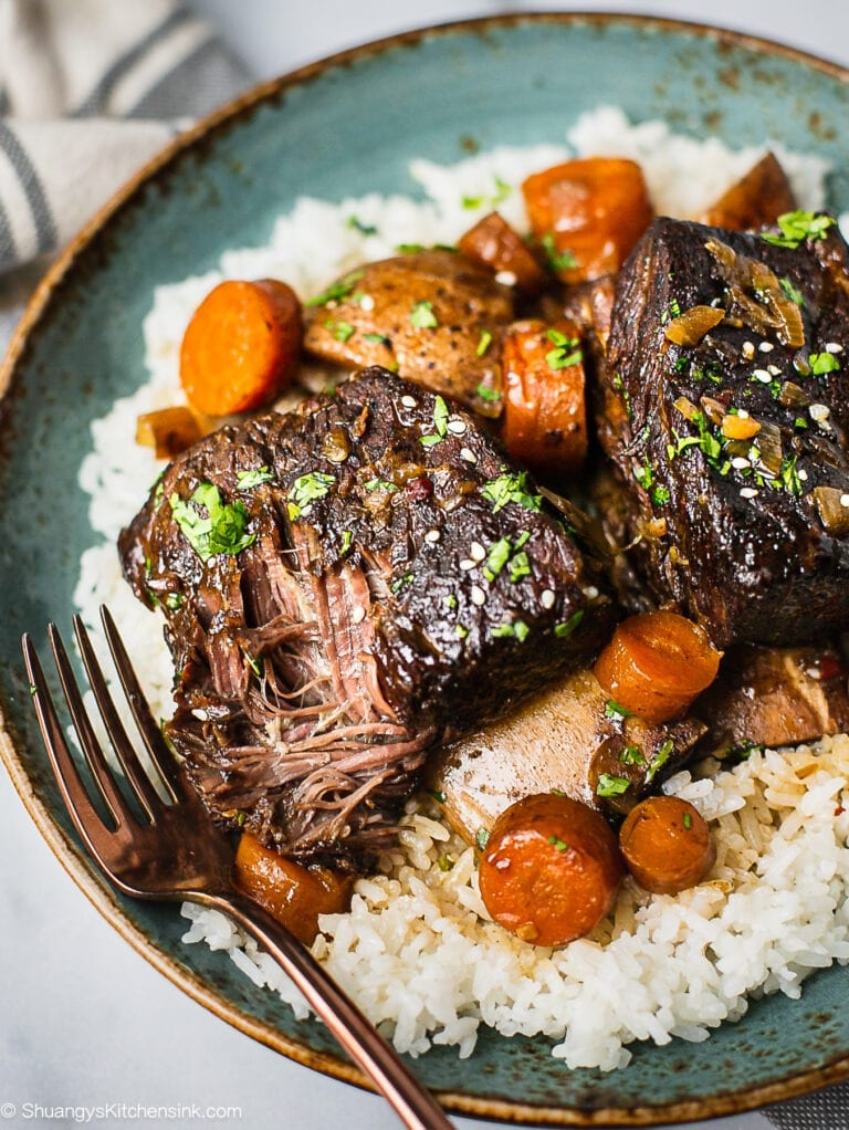 A plate of slow cooker Korean short ribs served with jasmine rice. There are carrots, potatoes in it and garnished with cilantro.. There is a fork getting a piece of beef that's falling off the bone.