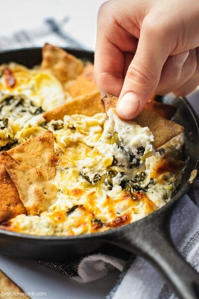 A cast iron skillet full of baked spinach artichoke dip. There is a hand holding a pita chip dipping in.