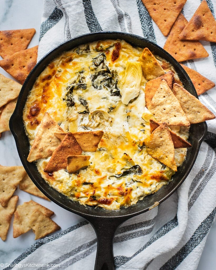 A cast iron skillet full of healthy spinach artichoke dip. There is a hand holding a pita chip dipping in.