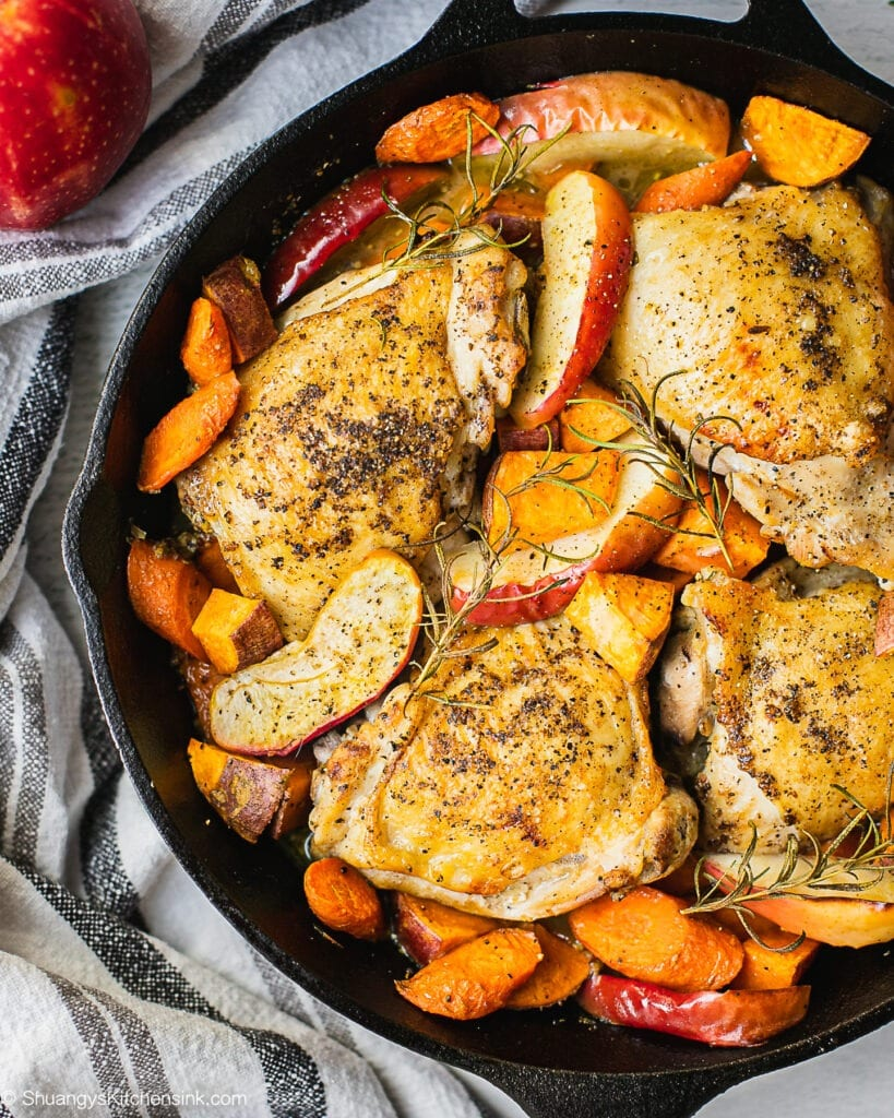 Freshly out of the oven cast iron skillet chicken thighs, fall chicken recipe made with apples, carrots, sweet potatoes and rosemary.