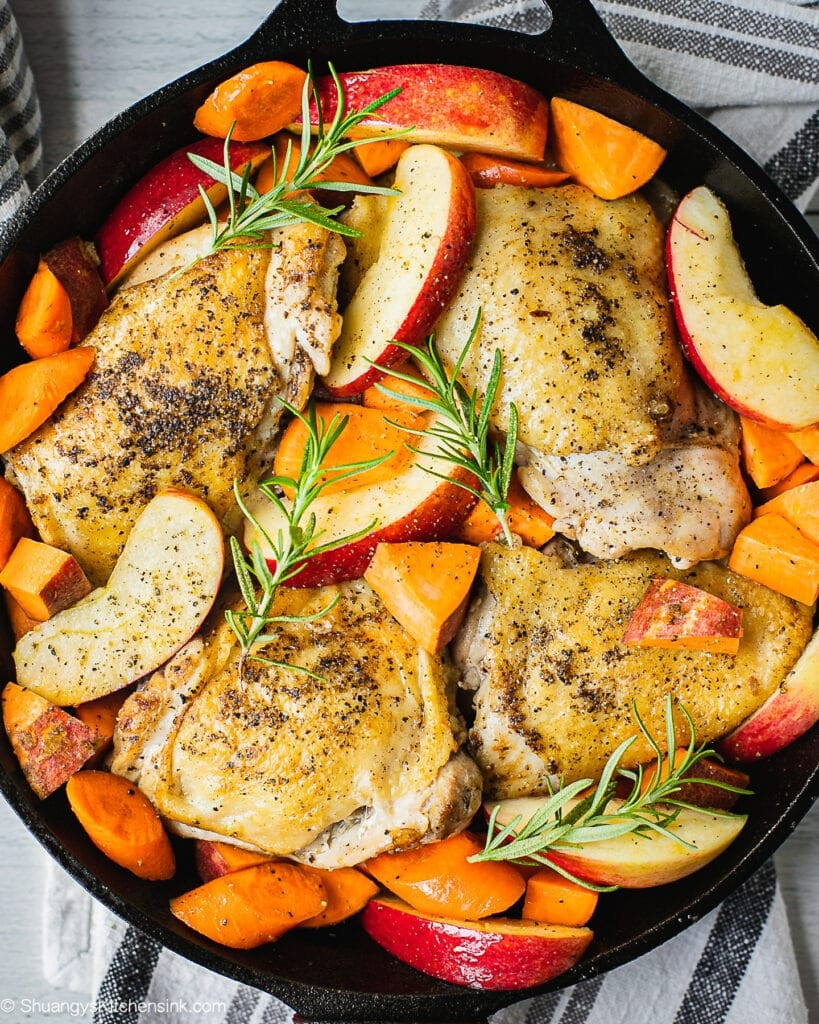 A cast iron pan with chicken, apples, sweet potatoes and carrots. There are springs of fresh Rosemary