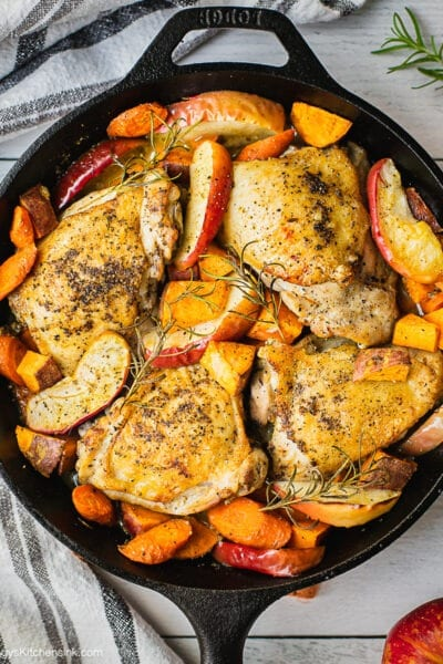 Cast iron skillet chicken that just came out of the oven. Apple cider chicken is cooked to crispy golden, apples, carrots and sweet potatoes are tender.