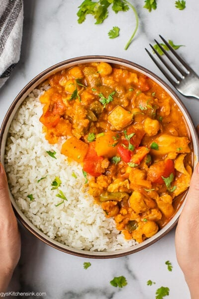 A bowl of Instant Pot Pumpkin Curry recipe served on a bed of rice. There are two hands holding this cozy and hearty one pot savory pumpkin recipe.