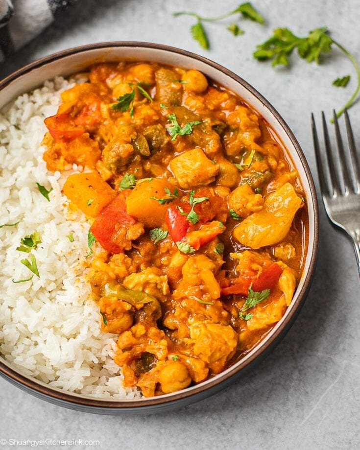 A bowl of pumpkin chickpea curry served on a bed of jasmine rice. Perfect for the chili weather.