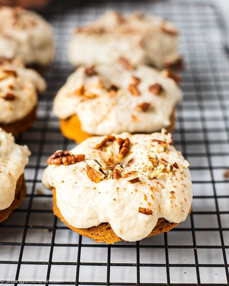 Freshly baked pumpkin spice donuts on a cooling rack ready to be glazed. They are packed with pumpkin spice, almond flour, pumpkin puree. It is topped with paleo, gluten free maple cashew icing and sprinkle of pecans.