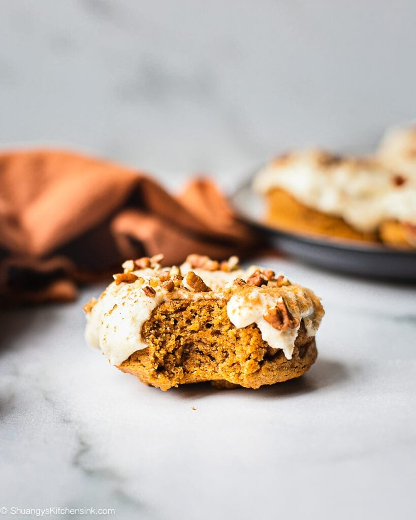 there is a pumpkin donut topped with vegan cashew cream cheese frosting sprinkled with chopped walnuts. Someone has taken a bite from the baked donut
