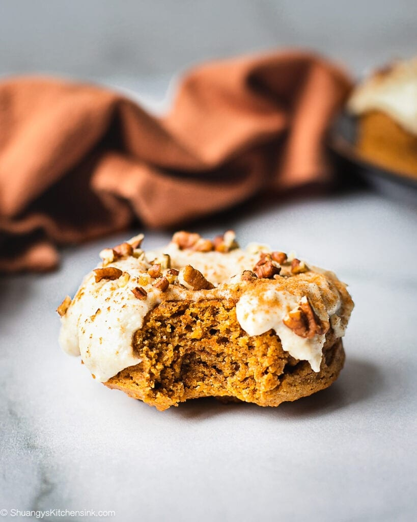 A piece of baked pumpkin donuts packed with pumpkin spice, almond flour, pumpkin puree. It is topped with paleo, gluten free maple cashew icing and sprinkle of pecans. There is a fall themed orange towel in the back.