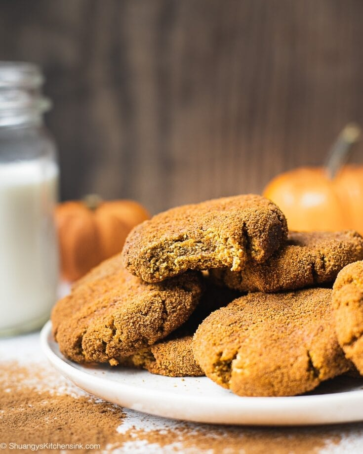 A plate of pumpkin snickerdoodle cookies coated with cinnamon sugar. There is a glass of milk and 2 little pumpkins in the background. There is also a bite into one of the pumpkin cookies that appear to be soft and chewy in texture.
