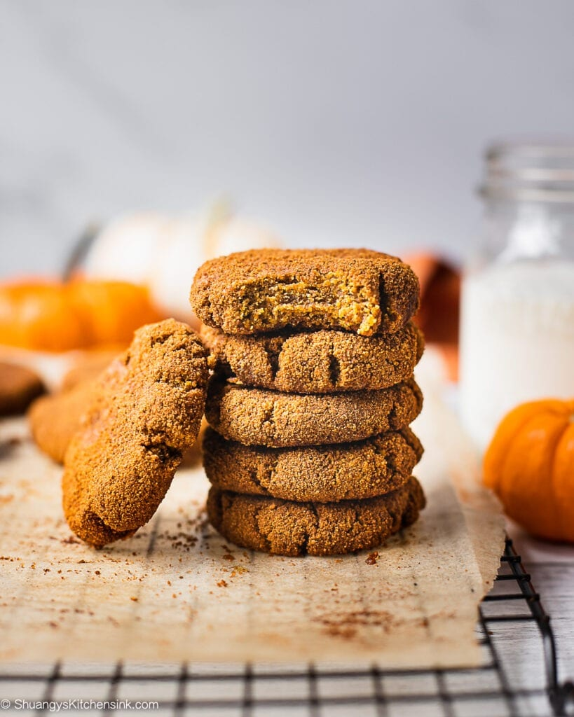 A stack of healthy pumpkin cookies on a piece of parchment paper. There is a glass of milk 2 little pumpkins in the background. The pumpkin spice cookie on top has a bite in it which make it look like a soft pumpkin cookie.