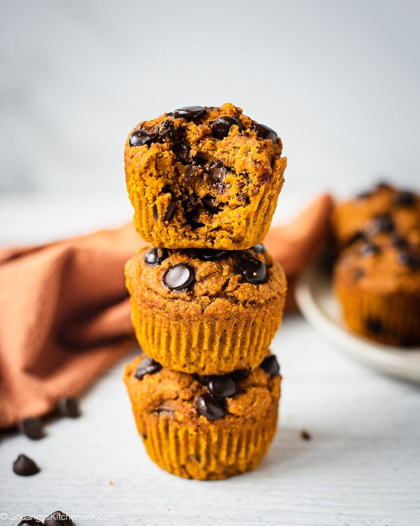 A stack of three healthy pumpkin chocolate chip muffins. There is a bite in the muffin on top.