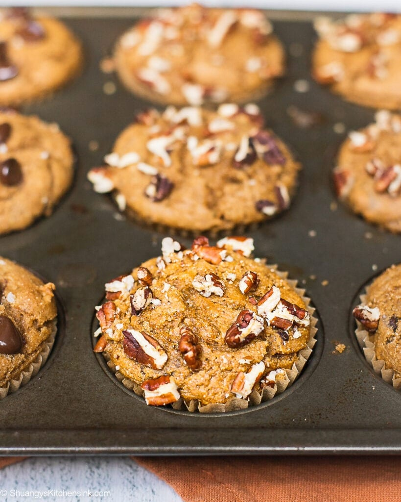 A muffin pan with freshly baked sweet potato muffin batter, half topped with chocolate chips, half topped with chopped pecans.