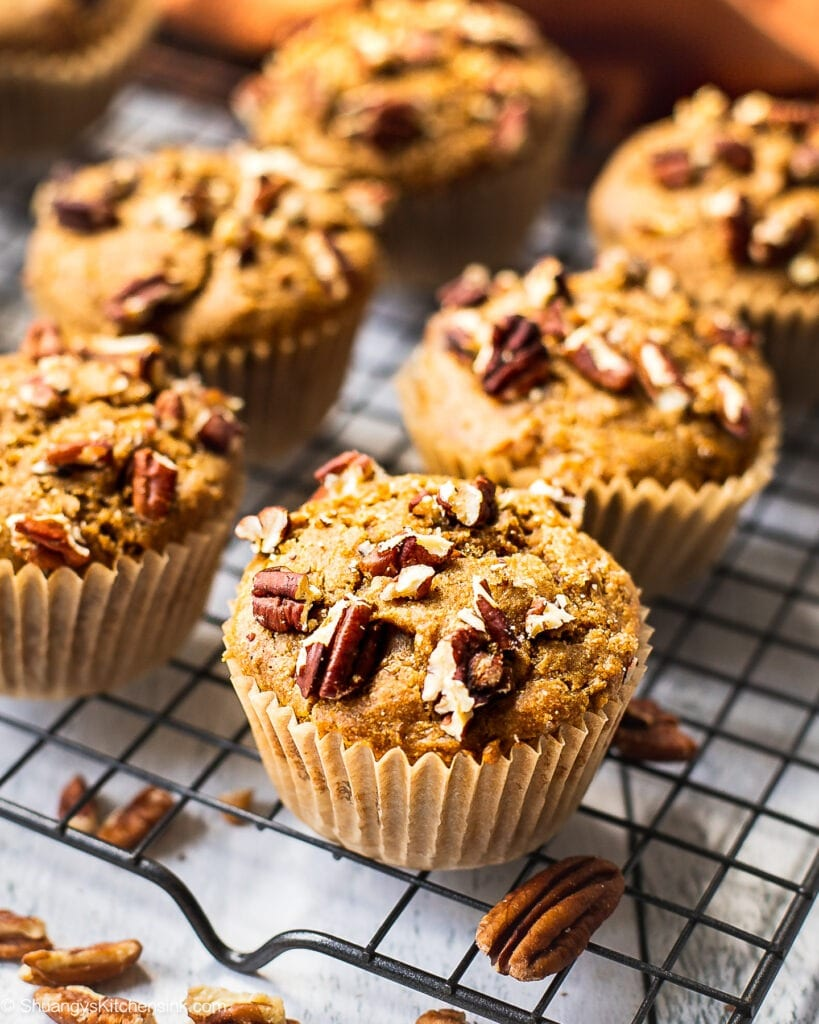 Freshly baked sweet potato muffin batter, half topped with chopped pecans on a cooling rack.