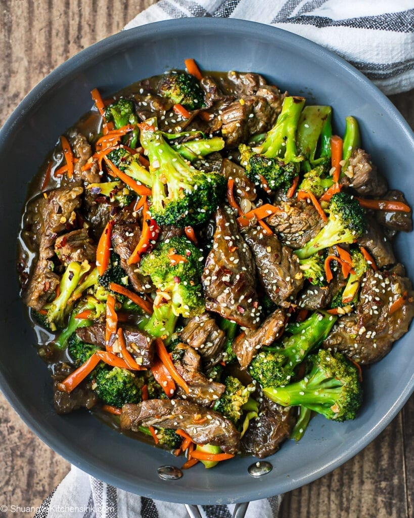 A pan of beef and broccoli stir fry with carrots and sesame seeds on top.