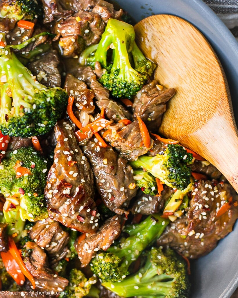 A pan of beef and broccoli stir fry with carrots and sesame seeds on top. There is a wooden spoon inserted in the tender beef flank steak.