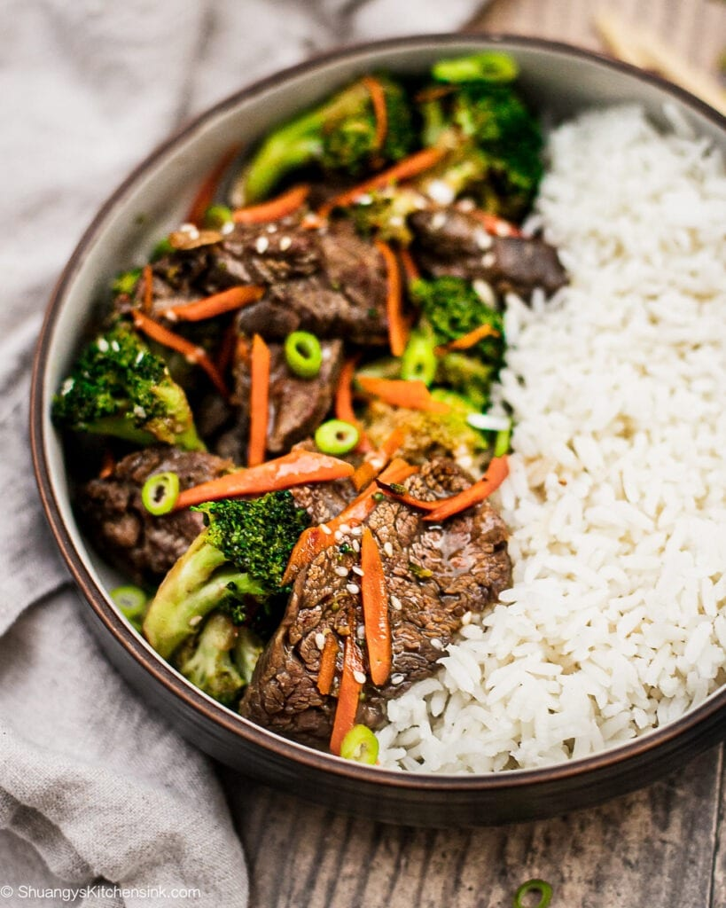 A bowl of healthy beef and broccoli stir fry served with jasmine rice for an authentic Chinese cuisine.