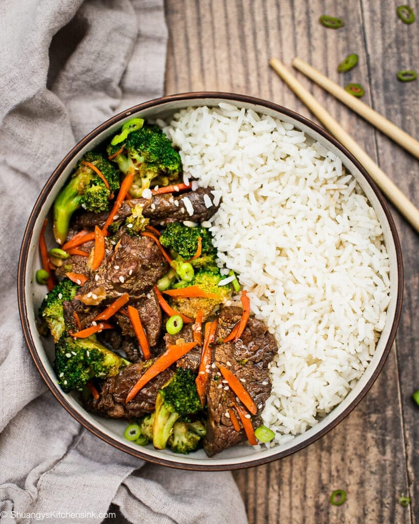 A bowl of healthy beef and broccoli stir fry with rice. there are green onion garnish on top and a pair of chopsticks on the side.