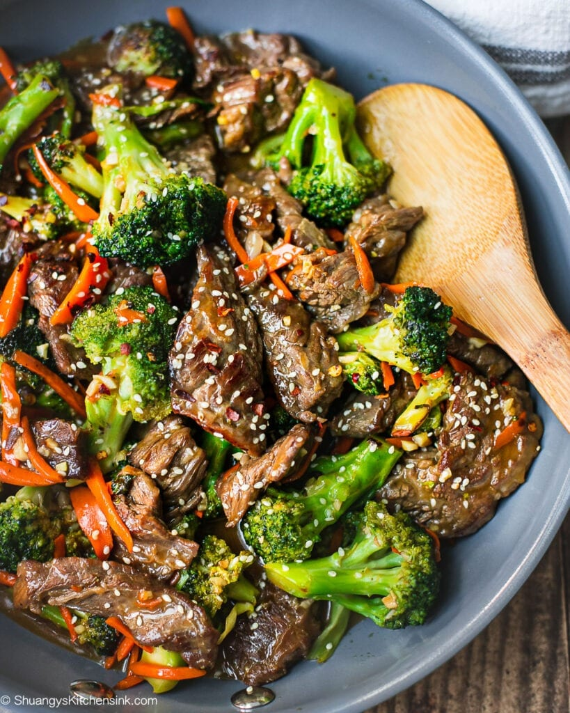 A pan of beef and broccoli stir fry with carrots and sesame seeds on top. There is a wooden spoon inserted in the tender beef flank steak.A pan of beef and broccoli stir fry with carrots and sesame seeds on top. There is a wooden spoon inserted in the tender beef flank steak.