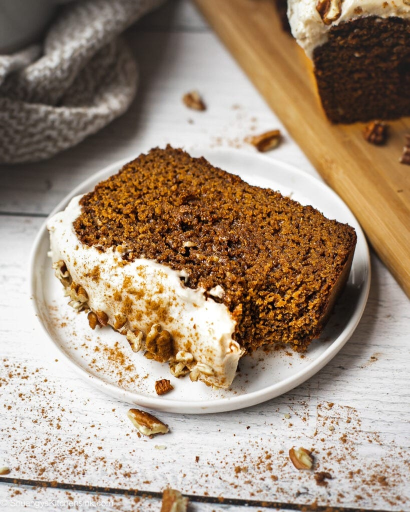 A slice of copycat starbucks gingerbread loaf with healthy cream cheese frosting. There are pecan pieces and cinnamon on top. There is a bite on the gingerbread loaf.