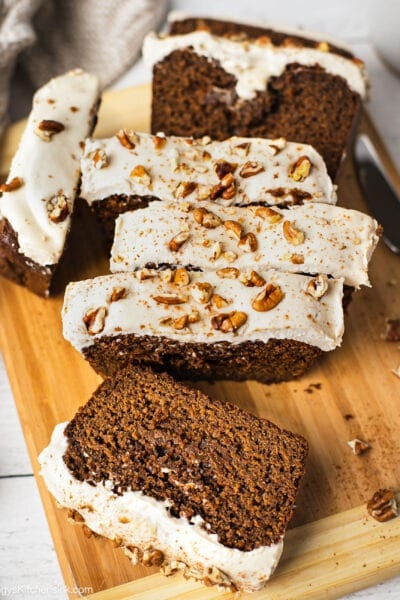 A loaf of slice paleo ginger bread loaf topped with cashew cream cheese frosting that makes it healthy and dairy free. There are pecan pieces on top of the gingerbread loaf.