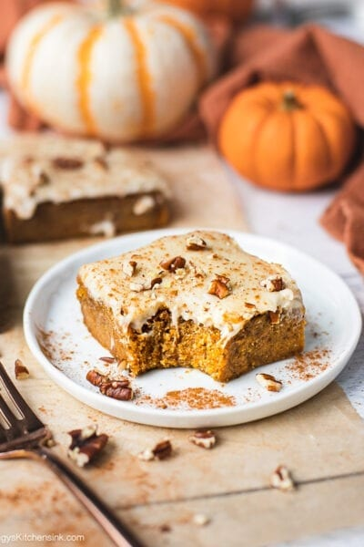A piece of pumpkin bar with cream cheese frosting on a little plate. There are pumpkin spice and pecans sprinkled on top. There is a bite in the middle. The pumpkin bar appears to be soft and chewy.