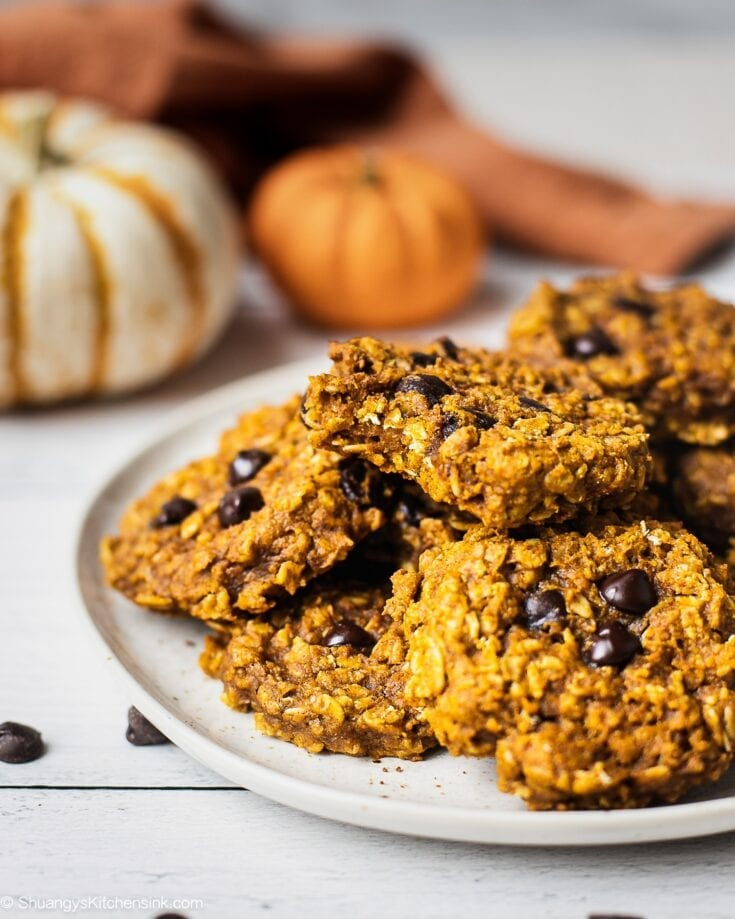 A plate of pumpkin oatmeal cookies with chocolate chips. There are a couple pumpkins in the background.