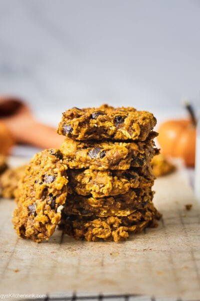 A stack of pumpkin oatmeal chocolate chip cookies. There is one oatmeal cookie leaning on the stack of the stack of cookies.
