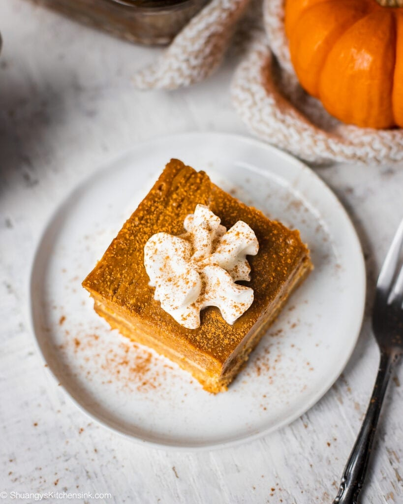 A piece of pumpkin square with almond flour pie crust is on a plate served with dairy free whipped cream and pumpkin spice.There is a whole plan of pumpkin pie bars in the background.