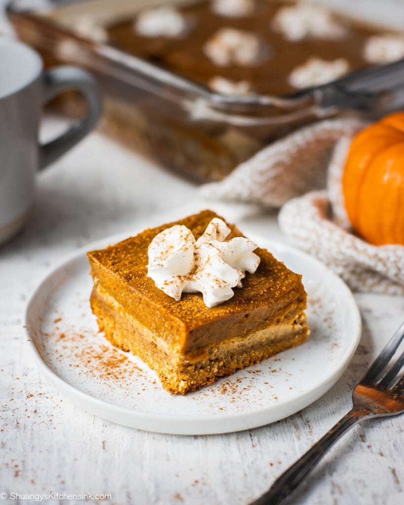 A piece of pumpkin pie bars with almond flour crust is on a plate served with dairy free whipped cream. There is a whole plan of pumpkin pie bars in the background.