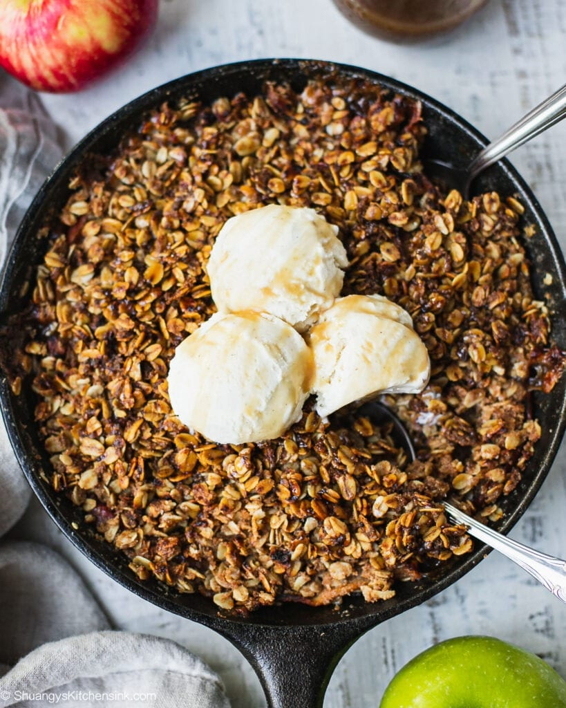 A skillet of healthy apple crumble topped with some vegan vanilla ice cream. There are two bowls of caramel apple crumbles served with ice cream on the side. There are also two apples on the board.