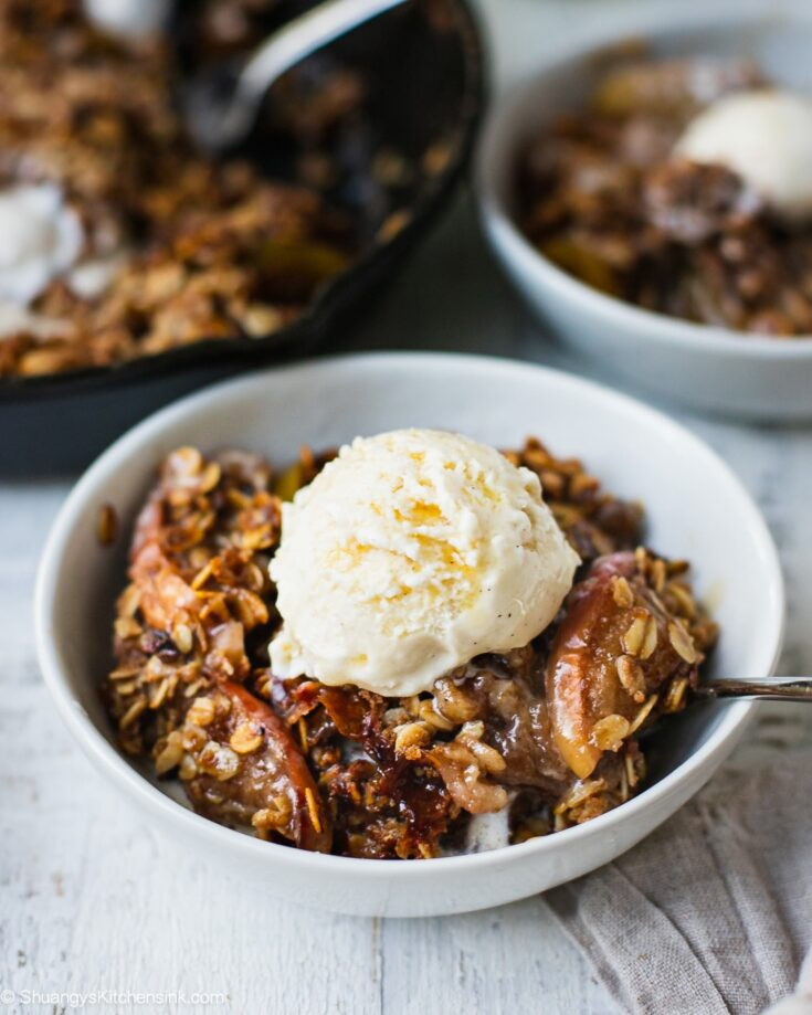 A bowl of caramel apple crisp with soft baked apples, crunchy oat crisp toppings and a scoop of dairy free vanilla ice cream. There is also drizzle of salted caramel sauce on top.